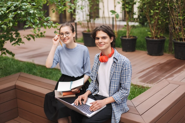 Couple of smiling students sitting on bench with books and laptop and happily