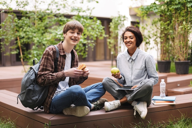 Couple of smiling students sitting on bench with sandwich and green apple and happily