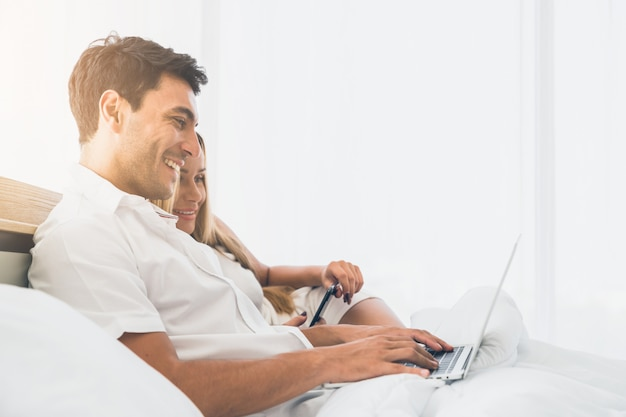 Couple smiling very happy while using laptop computer together on bed early morning