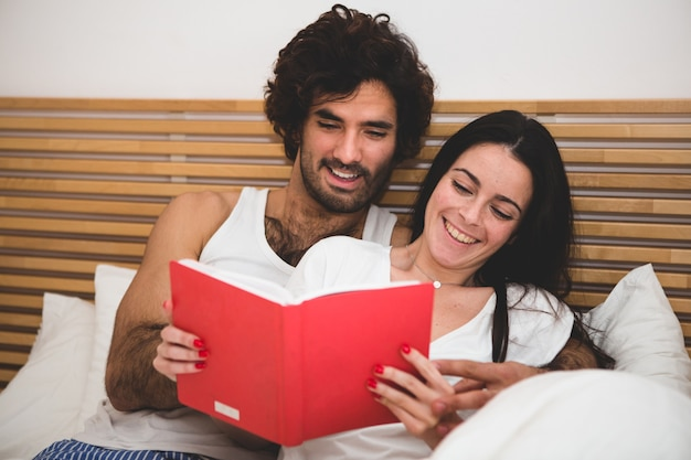 Couple smiling while reading a book in bed