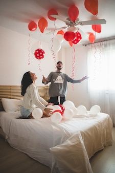 Couple smiling with hands raised looking at the ceiling full of heart shaped balloons