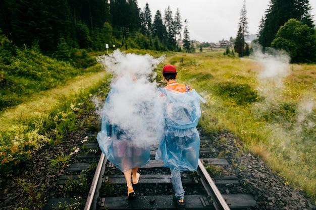 Couple of smoking travelers walk along railroad at nature