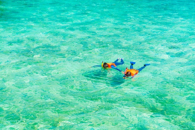 Couple snorkeling in tropical maldives island .