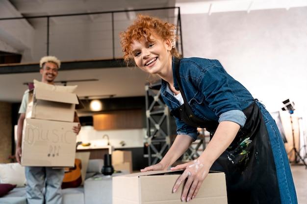 Пара сортирует вещи из картонных коробок после переезда в новый дом
