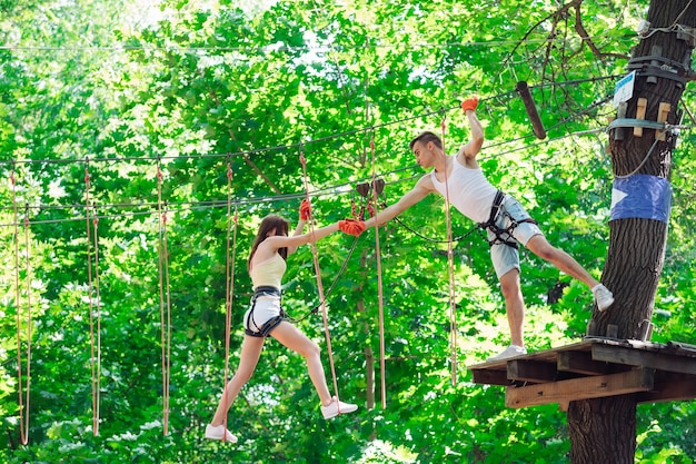 Couple spend their leisure time in a ropes course. man and woman engaged in rock-climbing,
