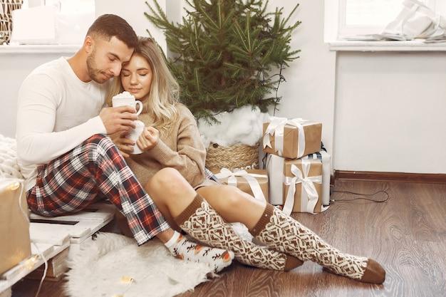 カップルはクリスマスの飾りと家で時間を過ごします