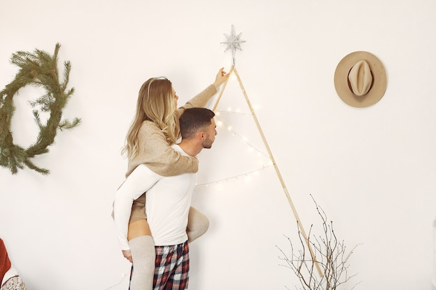 Пара проводит время дома с рождественскими украшениями