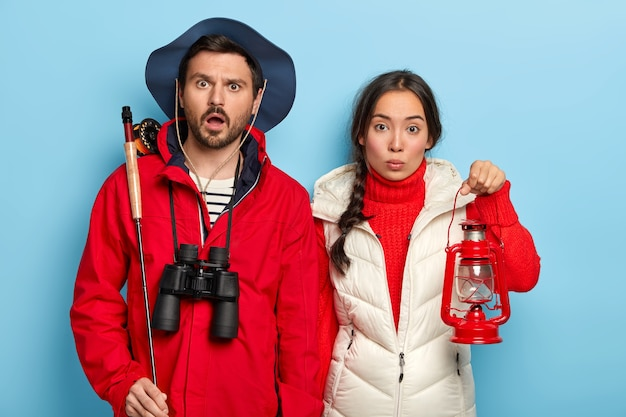 Couple spend weekend together in nature, going to have night fishing, carry kerosene lamp and fishing rod, wear warm casual clothes, stand over blue wall