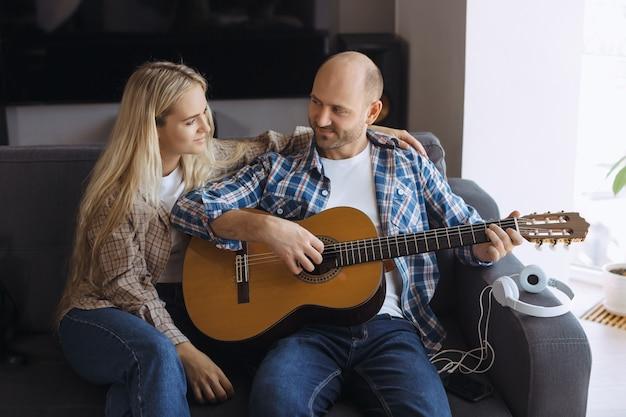 Пара проводит время дома, играя на гитаре