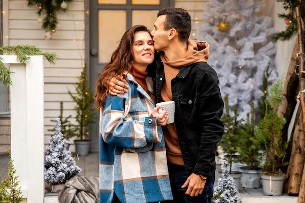 検疫中に屋外で時間を過ごすカップル少年は頬に彼のガールフレンドにキスします
