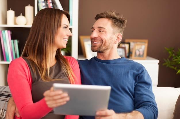 自宅でデジタルタブレットと一緒に時間を過ごすカップル