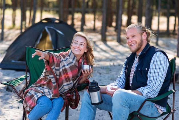 テントの横で一緒に時間を過ごすカップル