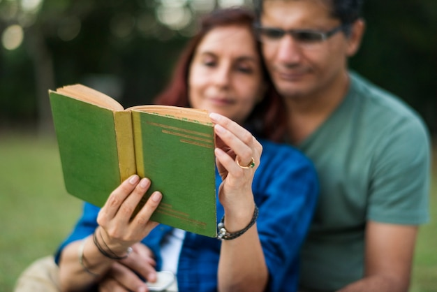 Couple spending time together reading a novel on a picnic in the jungle