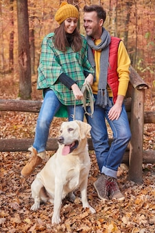 Couple spending time with dog in forest