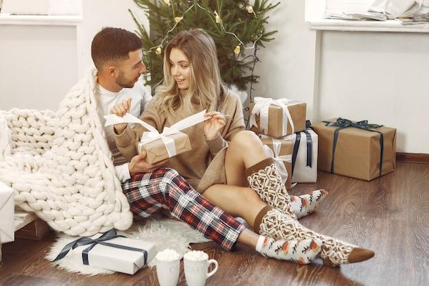 カップルはクリスマスの飾り付けで家で時間を過ごします