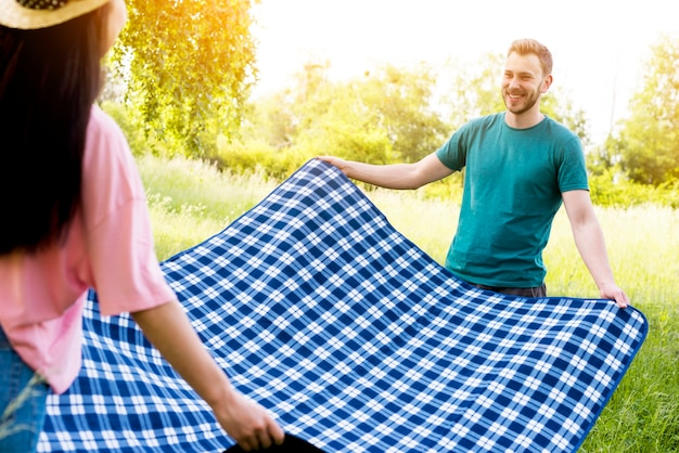 Couple spreading blue tablecloth for picnic
