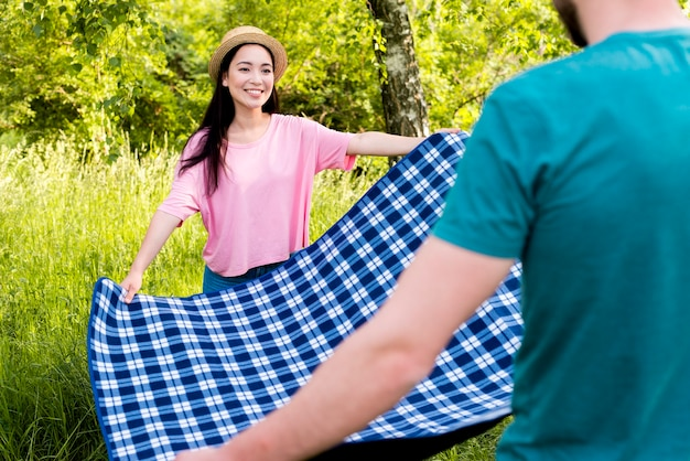 Couple spreading checkered plaid for picnic