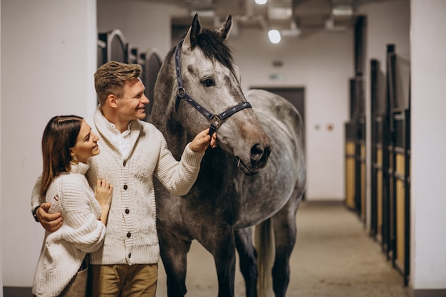 Couple in stable with horse