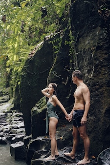 Couple stand under a large waterfall