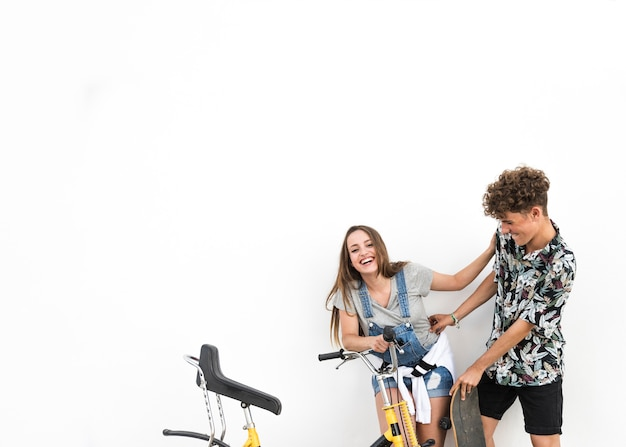 Couple standing against white backdrop holding bicycle making fun