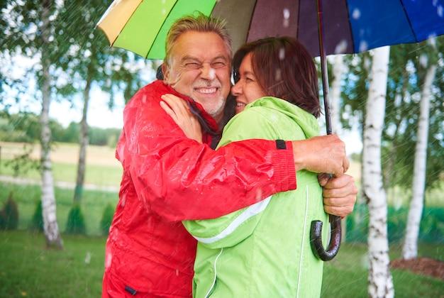 傘の下に立って抱きしめるカップル
