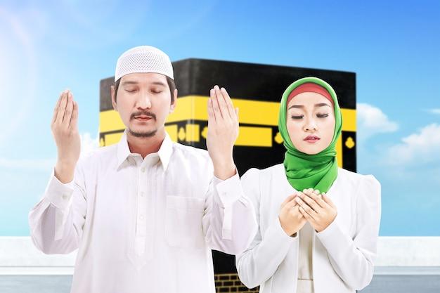 Пара стоит и молится вместе с видом на каабу и фоном голубого неба