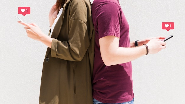 Couple standing back to back using cellphone with love messages icons against wall
