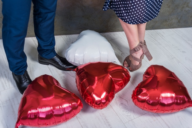 Couple standing on floor with heart balloons