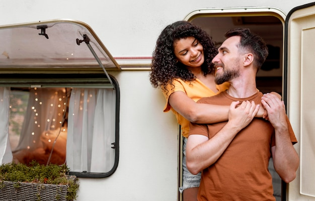 Couple standing in front of camper van and looking at each other
