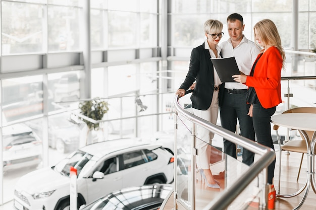 Couple standing hugging in interior of dealership with dealer.