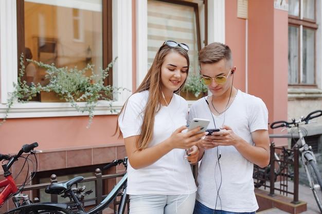 携帯電話が付いている都市に立っているカップル
