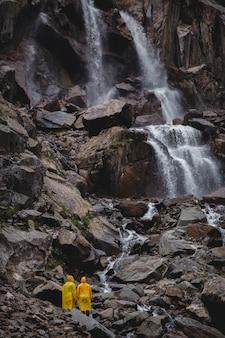 カップルは黄色のレインコートで立っています。後ろから背景ビューの滝。ライフスタイル