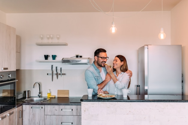 Couple standing in the kitchen of modern apartment and having breakfast together.