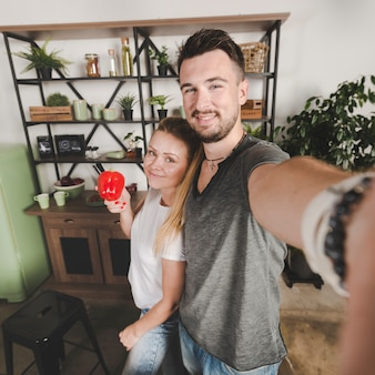 Couple standing in kitchen taking selfie