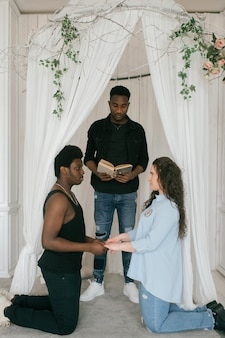 Couple standing on knees in front of wedding arch