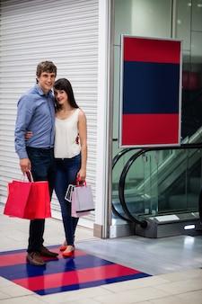 Couple standing near escalator in shopping mall