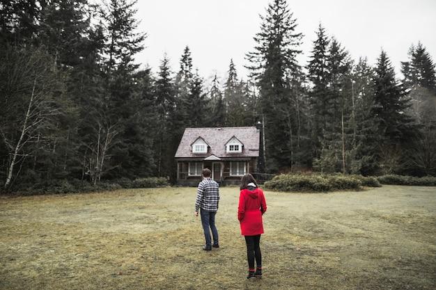森のシャックルの近くに立っているカップル