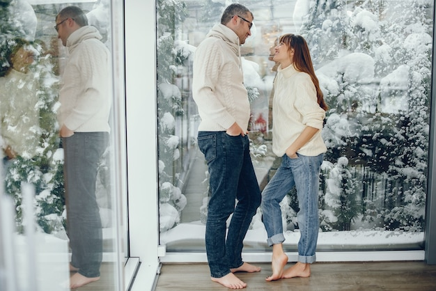 Пара стоя возле большого окна дома