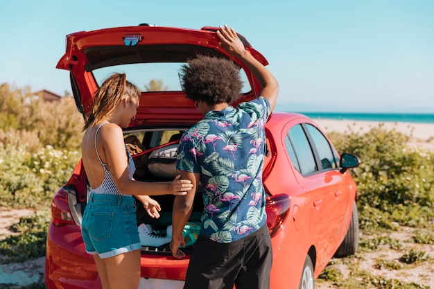 Couple standing near open trunk of car by seashore