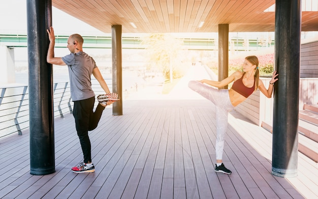 Couple standing near the pillar stretching her leg while doing exercise