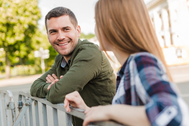Couple standing near railing looking at each other