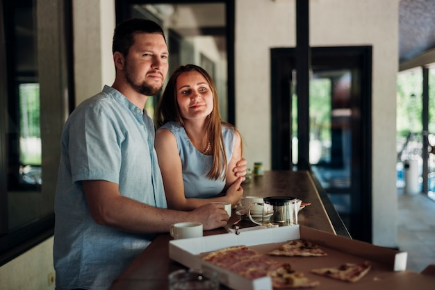 Couple standing near table with food leftovers