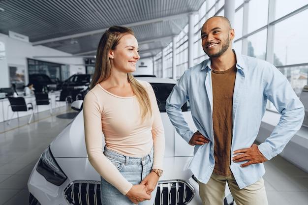 カーサロン内の新しい高級車の近くに立っているカップル