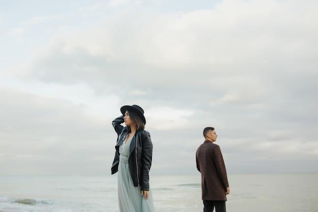 海沿いのビーチに立っているカップル