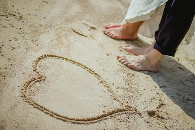 해변에 서 있는 커플. 모래 속의 신랑 신부는 마음을 그립니다.