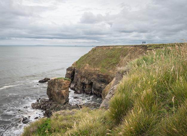 뉴질랜드 흐린 날 동안 바다의 전망을 즐기는 절벽의 가장자리에 서 있는 커플