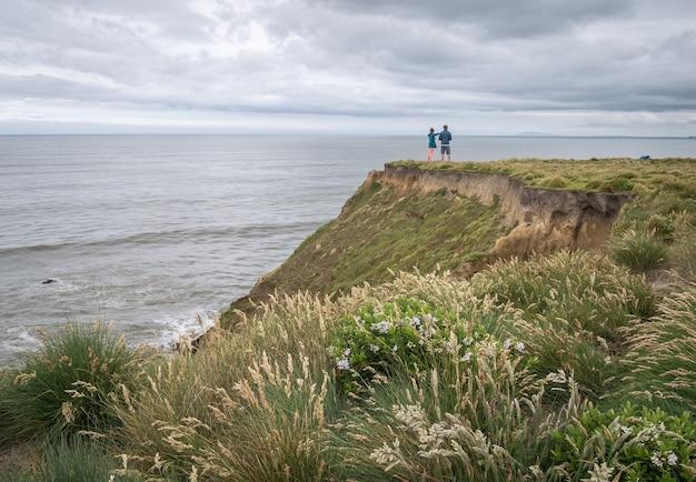 曇りの日ニュージーランドの間に海の景色を楽しむ崖の端に立っているカップル