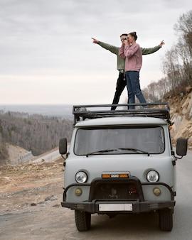 Пара стоя на фургоне полный выстрел