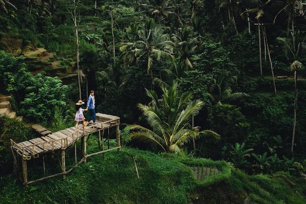 Пара, стоящая на деревянном мосту возле рисовых террас в бали, индонезия. держась за руки. романтическое настроение. тропический отдых. воздушный выстрел. на фоне кокосовых пальм.