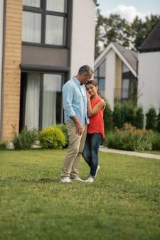 外に立っているカップル。週末に彼らのコテージの家の近くで外に立っている間抱き締めるカップル